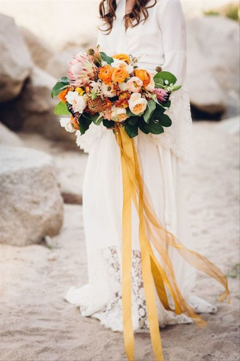 colorful yellow and peach wedding bouquet with garden roses, ranunculus and king protea