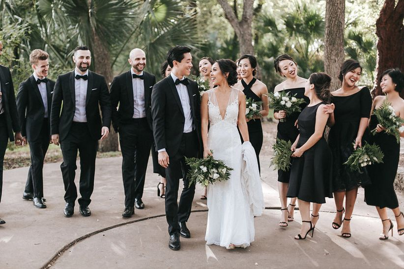 bridal party wearing black and white formal attire and bridesmaids carrying greenery bouquet