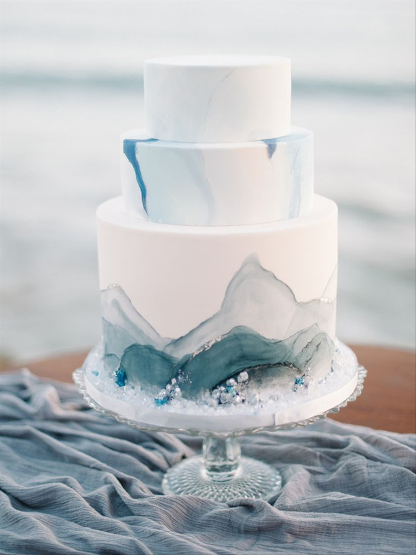 three-tier wedding cake with white fondant and blue watercolor decoration