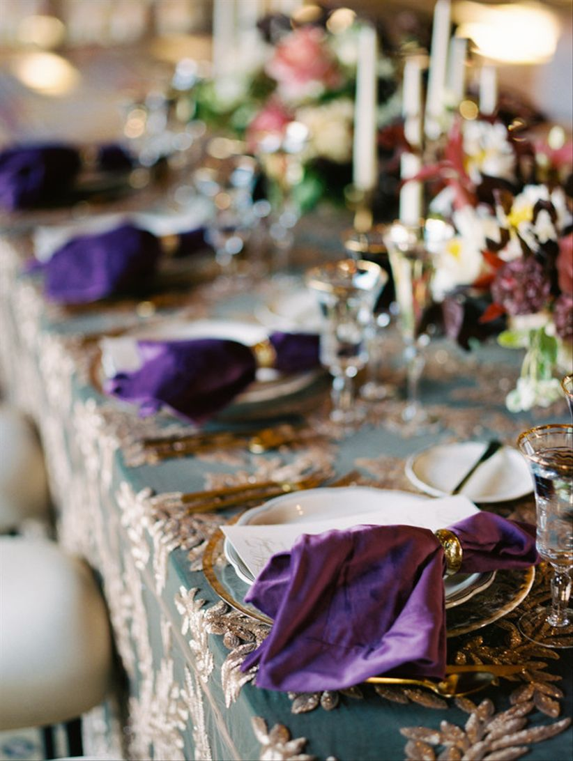 wedding place setting with dark green tablecloth, purple napkins and gold details