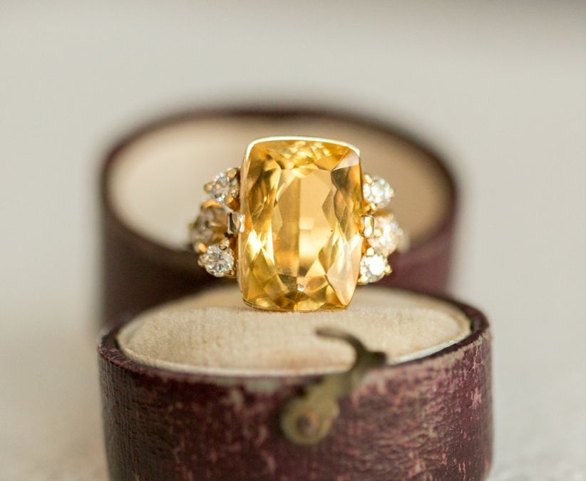 large yellow engagement ring with diamonds on both sides