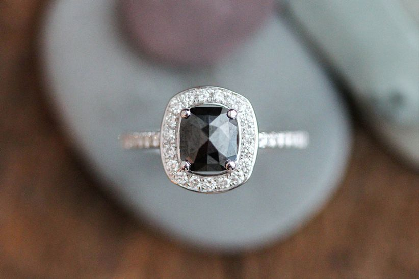 black engagement ring with cushion-cut onyx and diamond halo setting