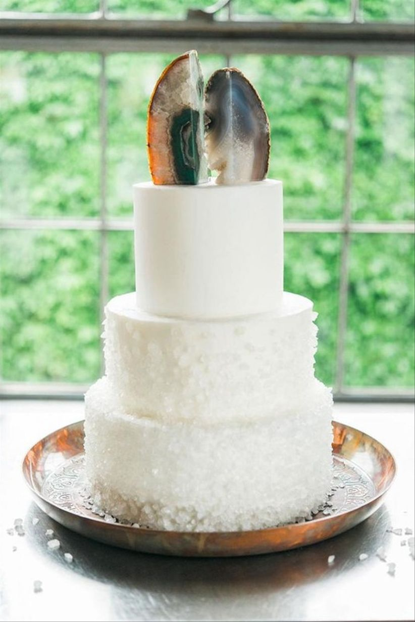 white three-tier wedding cake with geode cake topper