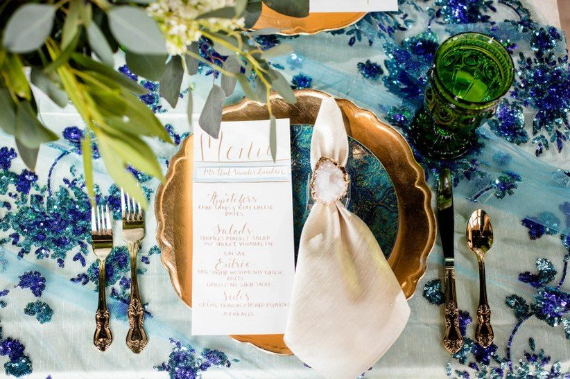 turquoise and gold wedding place setting with geode napkin ring and greenery