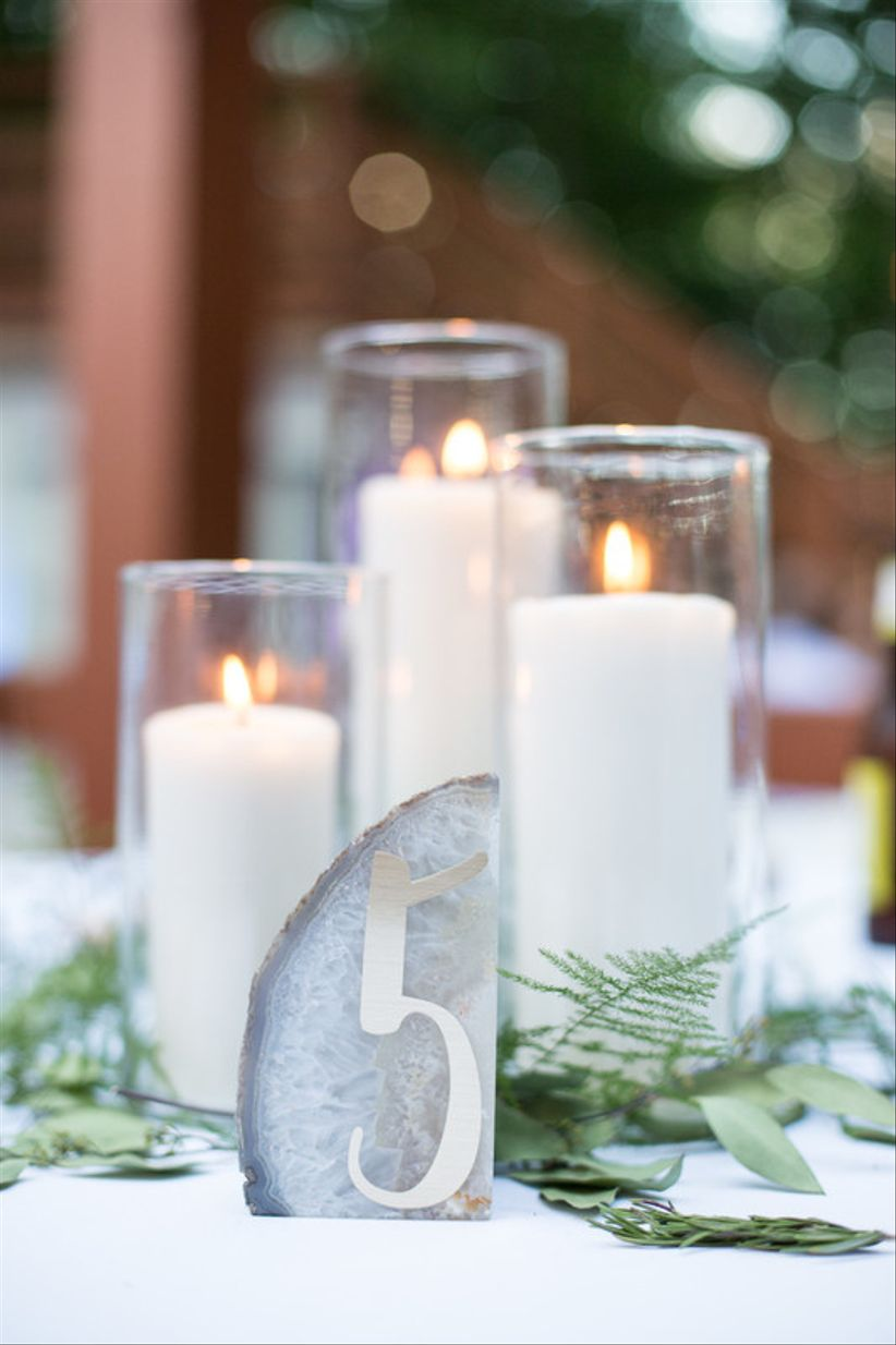 modern gray and white geode table number with white pillar candles and greenery