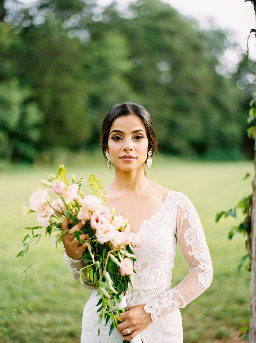 bride wearing lace illusion sleeve dress holding long stem bouquet with pink lisianthus