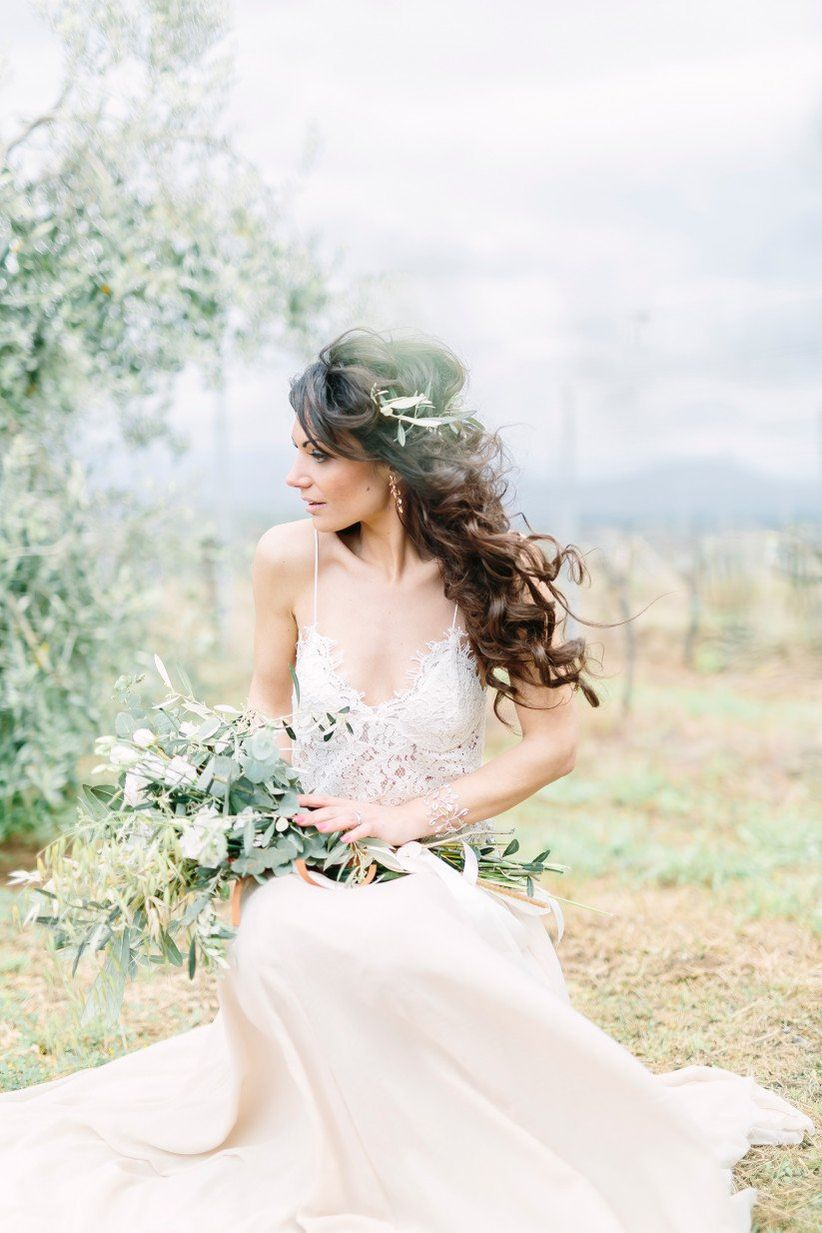 ethereal bride in Italy with flowy wedding dress and greenery presentation bouquet