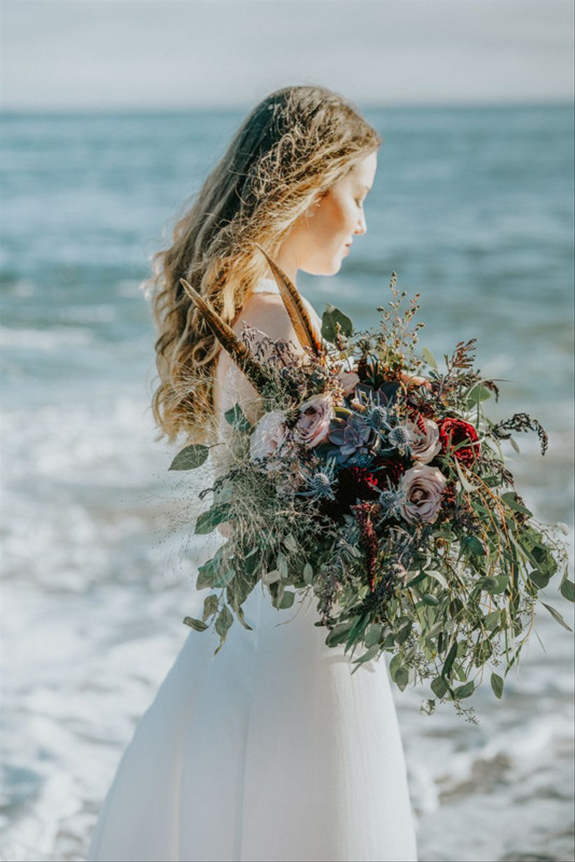 bohemian bride carrying oversized wedding bouquet with feathers and greenery