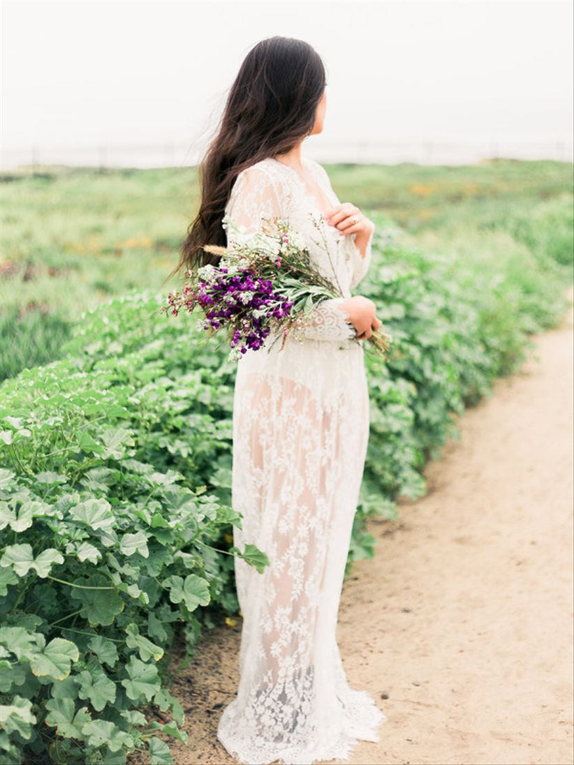 bride at bridal portrait session wearing lace maxi dress and holding purple presentation wedding bouquet