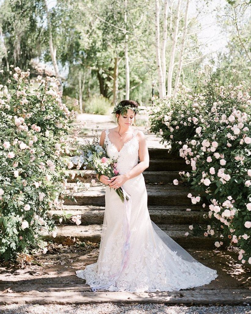 bride standing in rose garden carrying oversized wedding bouquet with pink flowers