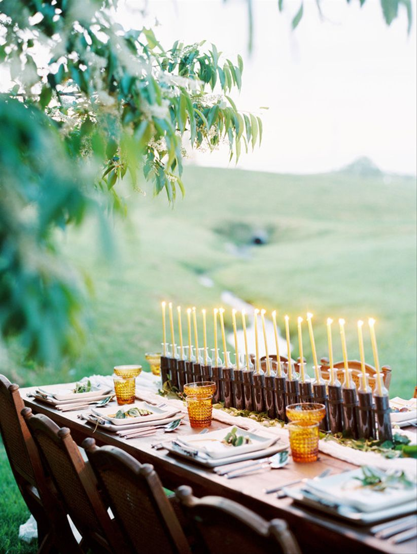 rustic outdoor wedding centerpiece with a row of tall taper candles and mustard yellow details