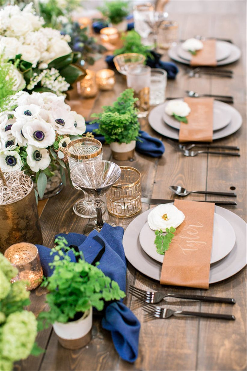 rustic wedding tablescape with cobalt blue napkins, potted plants and gold details