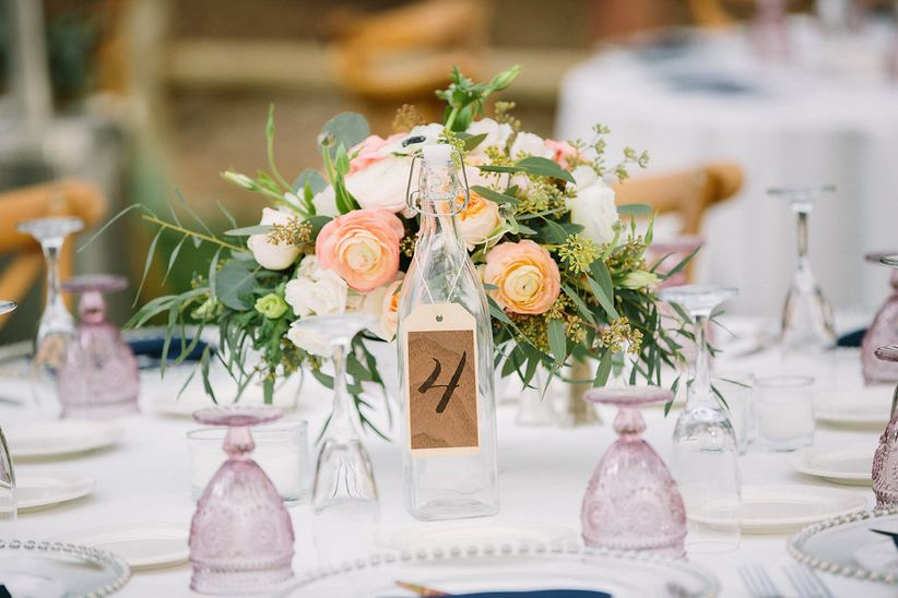 blush and greenery centerpiece with glass bottle table number