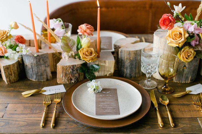 rustic wedding centerpiece with stacked logs and candles