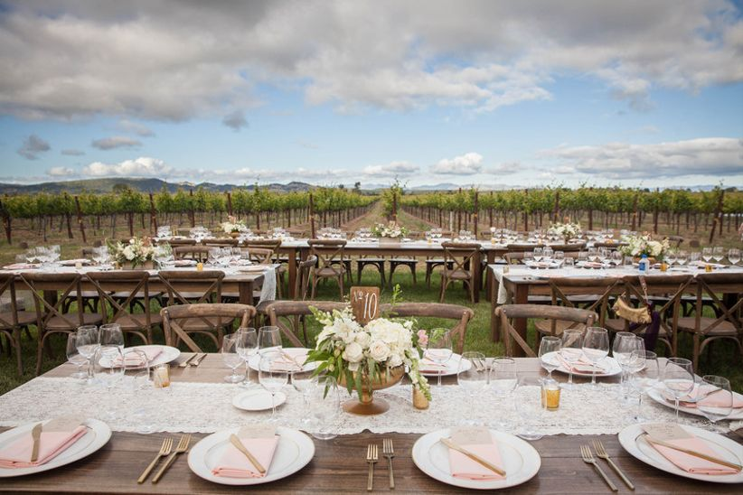 outdoor wedding reception with long banquet tables decorated with lace table runners and low centerpieces