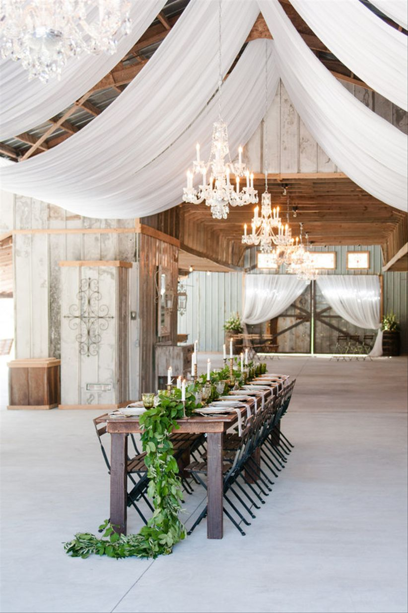 rustic wedding tablescape with long greenery runner and white taper candles