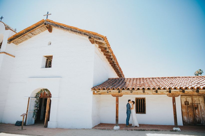 bride and groom pose in front of old mission church in Santa Barbara