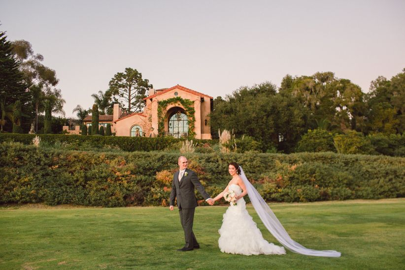 bride and groom walk and hold hands at outdoor garden wedding venue in Santa Barbara