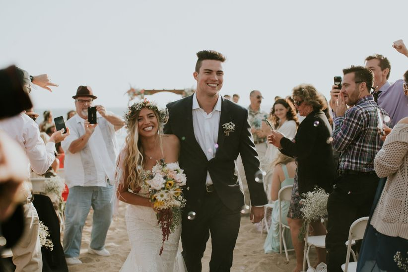 bride and groom smiling while walking down the aisle at beach wedding ceremony in Santa Barbara