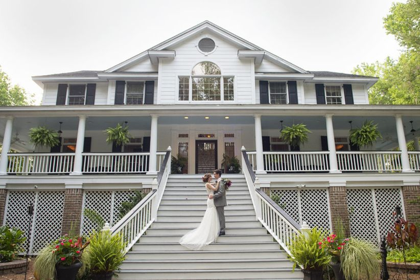 bride and groom pose in front of The Mackey House wedding venue in Savannah GA