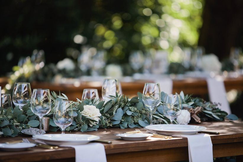 wedding reception tablescape with white plates, napkins and greenery centerpiece