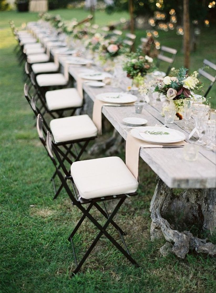long wedding banquet table with bistro chairs and place settings