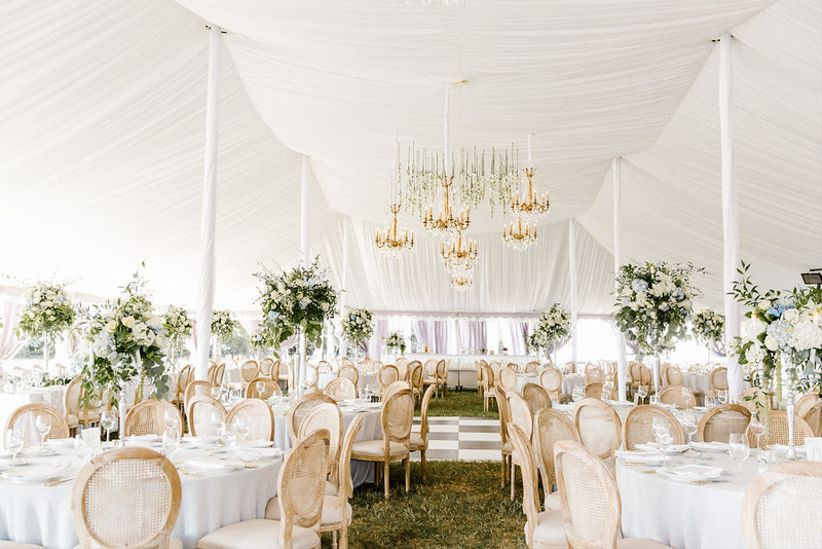 outdoor wedding reception tent with glamorous table settings, tall centerpieces and chandeliers