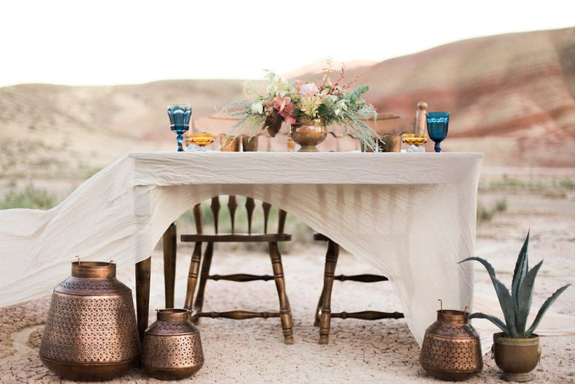 outdoor wedding sweetheart table at desert wedding venue with potted plants and centerpiece