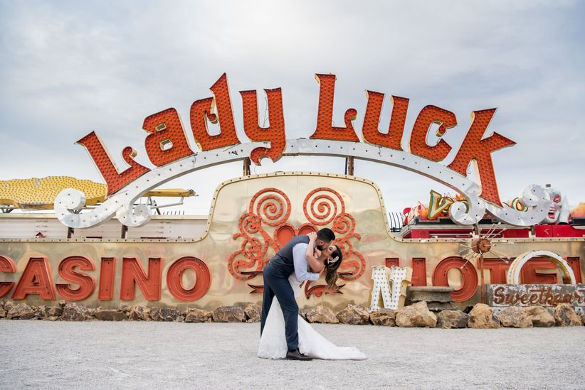 bride and groom pose in front of vintage Lady Luck casino sign at Neon Museum wedding venue in Las Vegas