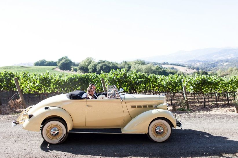 bride and groom sitting in vintage yellow convertible driving through Napa Valley vineyard
