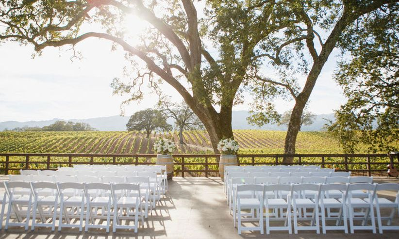 outdoor wedding ceremony napa wedding venue with empty white folding chairs arranged beneath a huge old tree and vineyards in the distance