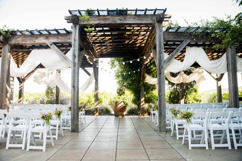 outdoor wedding ceremony with wooden pergola covered in wisteria vines, winery wedding venue in Sonoma California