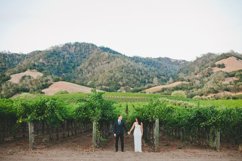 bride and groom hold hands in the vineyard at winery wedding venue in Sonoma