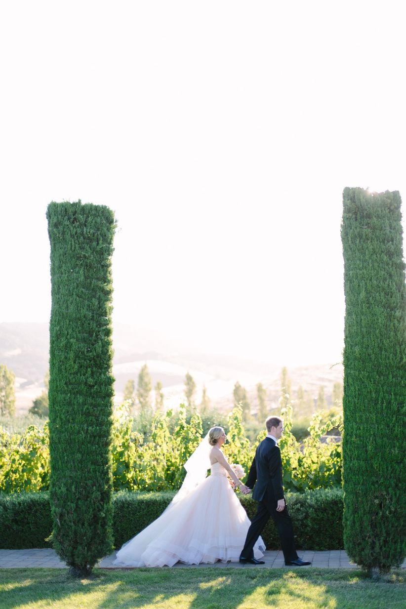 bride and groom walking through European style garden at winery wedding venue in Sonoma California