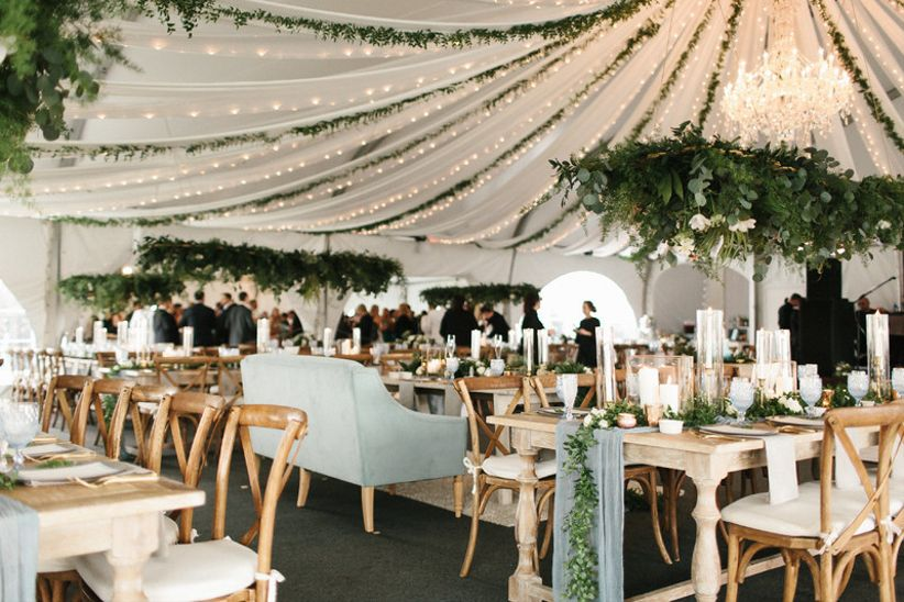 elegant garden-style wedding reception tent with greenery garlands and light strands