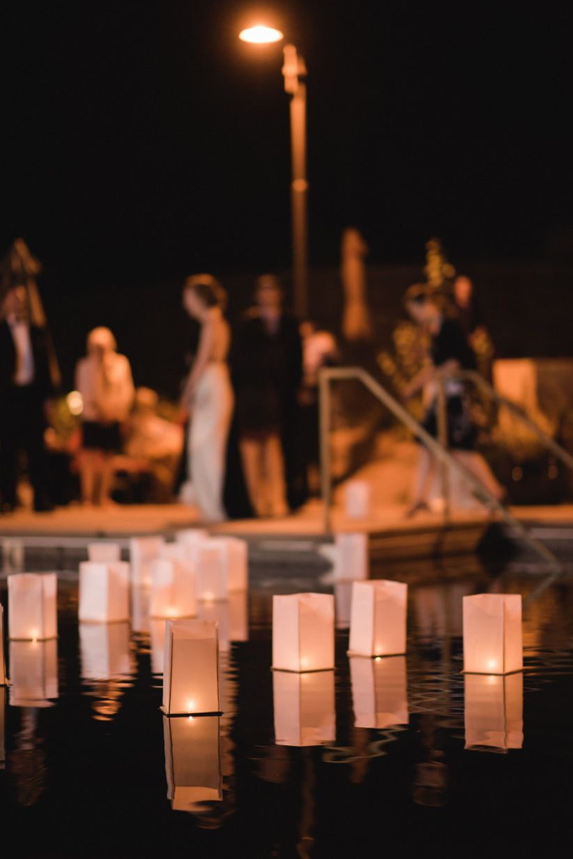 paper luminaries with votive candles floating in a pool at outdoor wedding reception