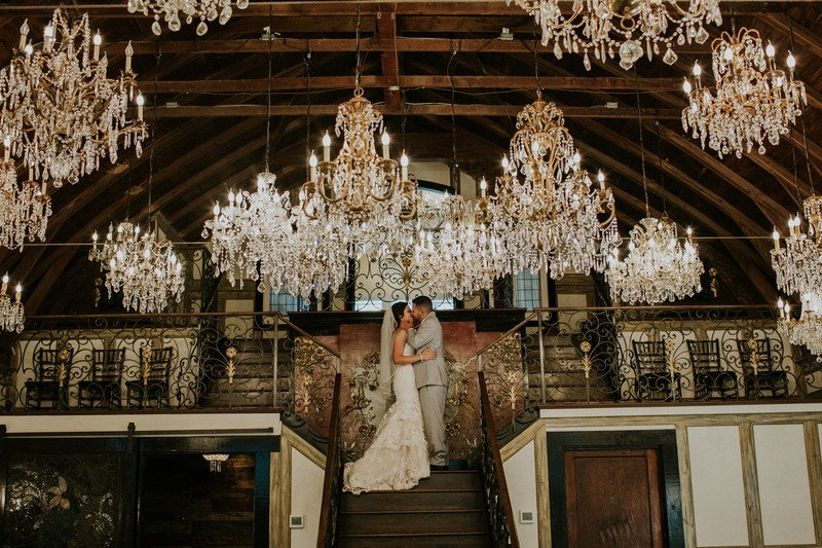 indoor wedding reception with crystal chandeliers and couple kissing