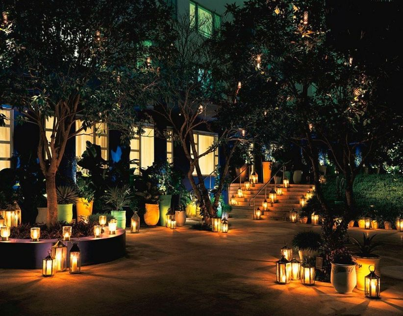 outdoor wedding venue at night with lanterns and candles illuminating the pathways