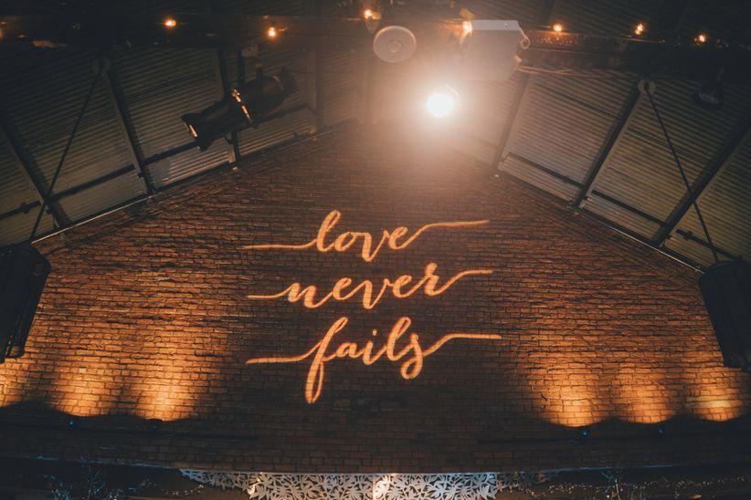 "custom wedding gobo wall projection that says ""love never fails"""