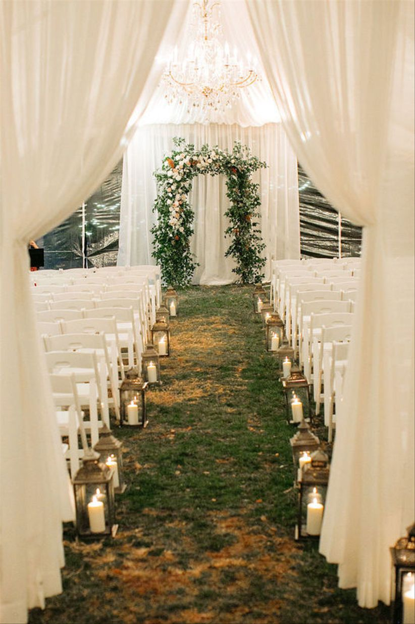 tented wedding ceremony with candle lantern aisle markers