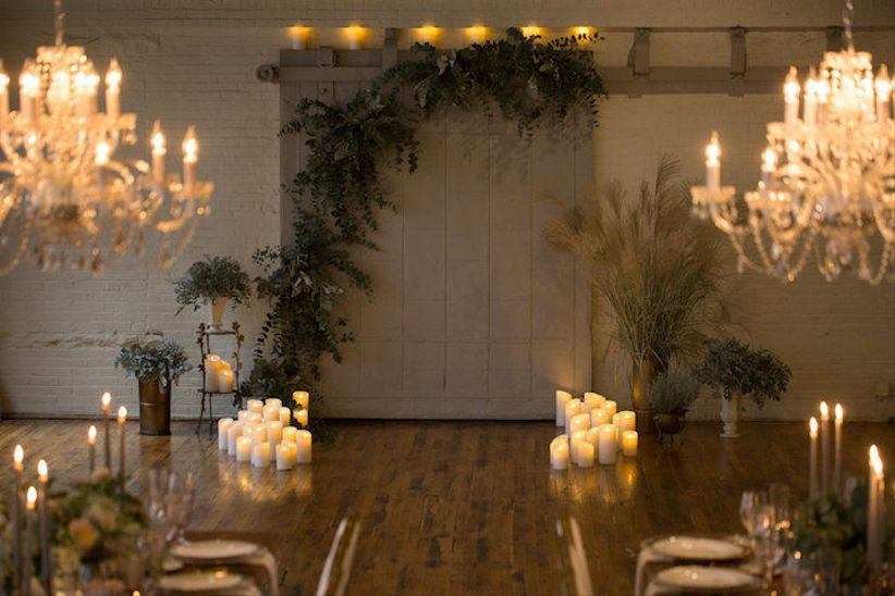 romantic wedding ceremony altar idea with white flameless candles and greenery backdrop
