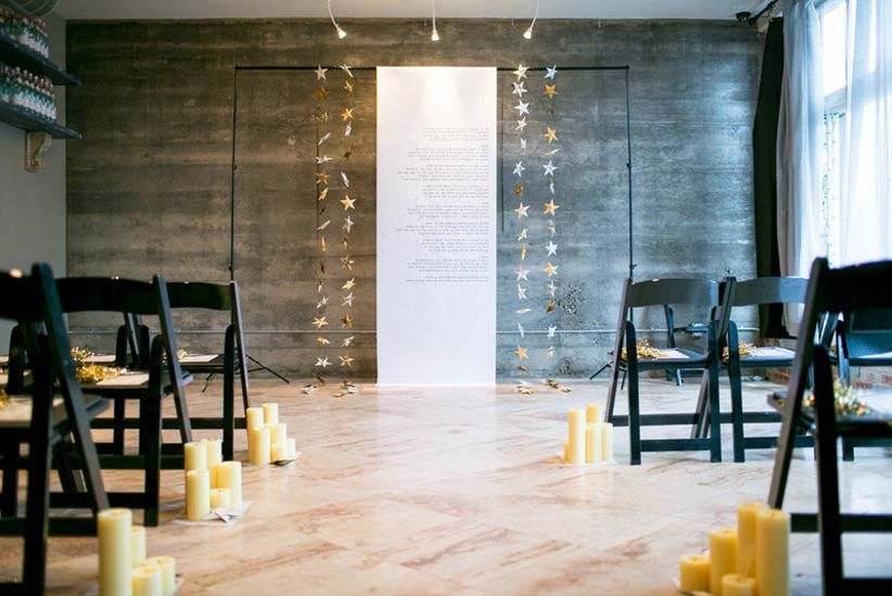 small indoor wedding ceremony with fabric and metallic star backdrop decorating the altar