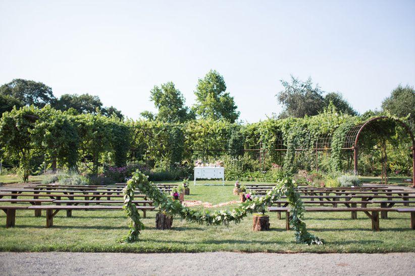 sunny outdoor garden wedding ceremony venue surrounded by vineyards