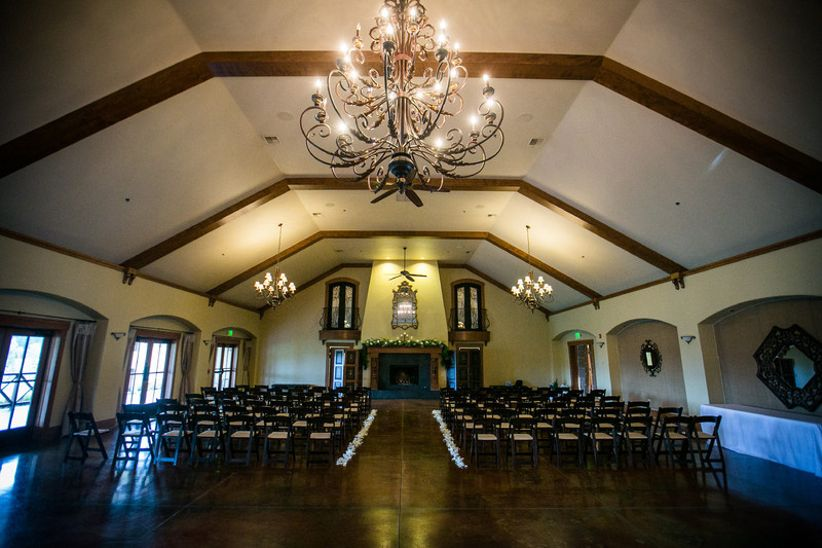 indoor wedding ceremony venue with beamed wood ceilings and chandeliers