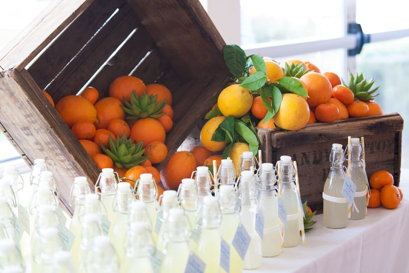 wedding favors on a table decorated with wooden crates and oranges