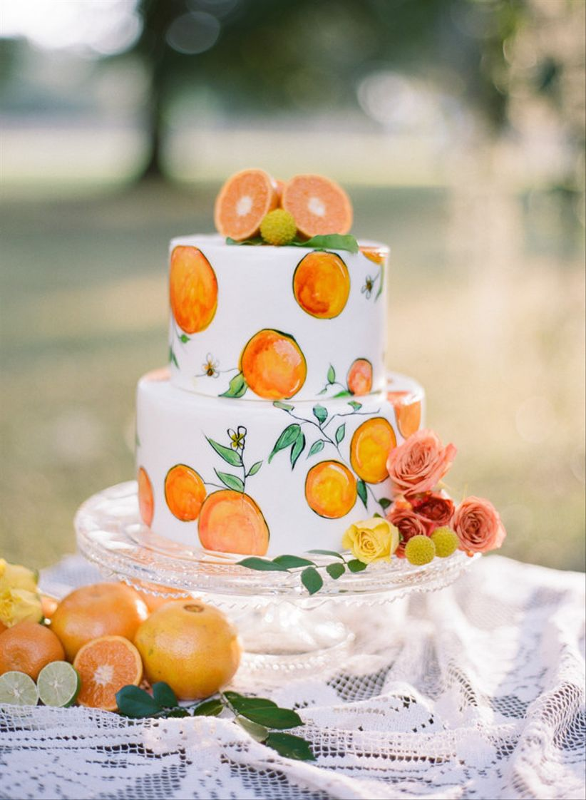 white fondant wedding cake with handpainted oranges and fresh orange slice topper