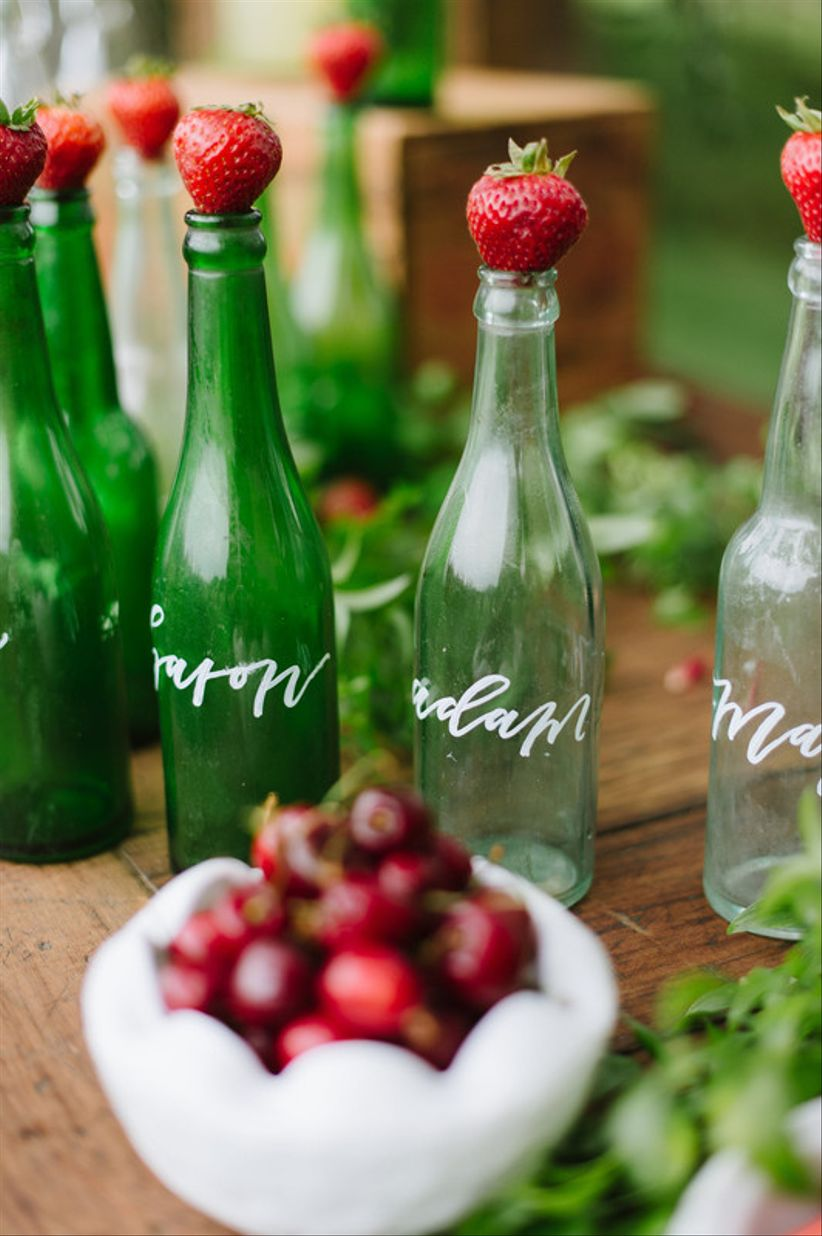 vintage wedding escort cards with glass soda bottles and fresh strawberries