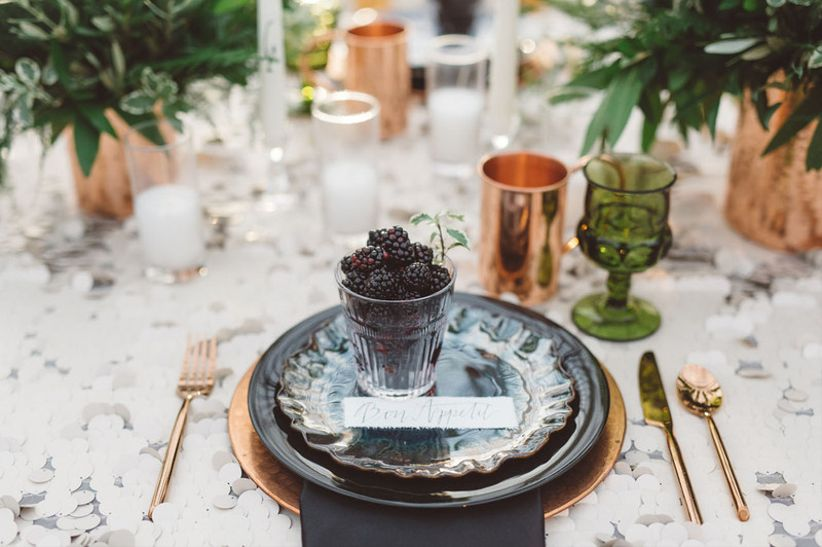wedding place setting with gold flatware and fresh blackberries