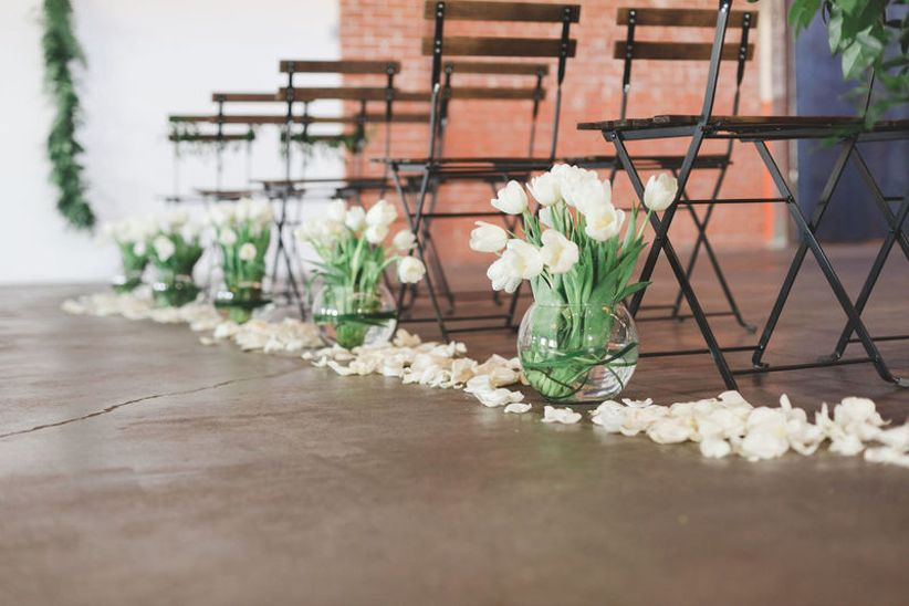 vases of white tulips are placed on the floor at the end of each row of folding chairs at indoor wedding ceremony