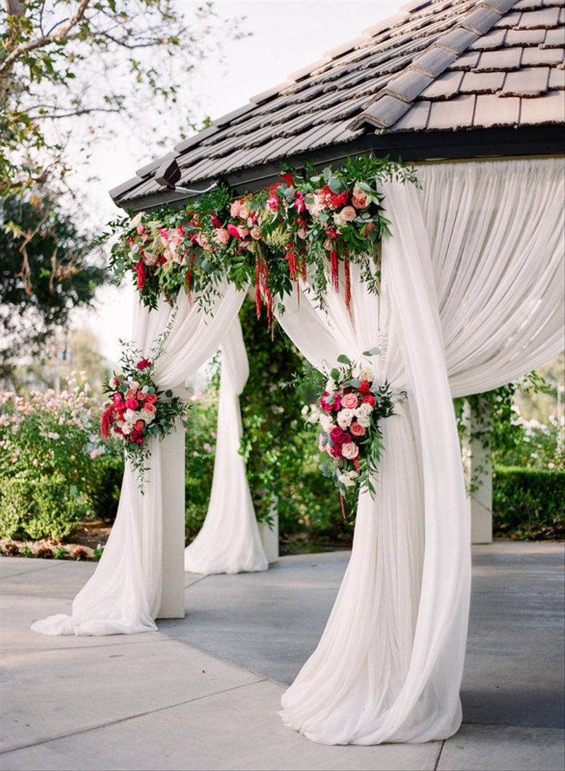 wooden gazebo is decorated with sheer white curtains tied back with floral arrangements on each post